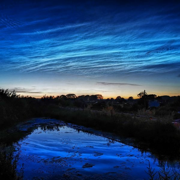 Noctilucent Clouds in the Sky and Reflected on the surface of a pond